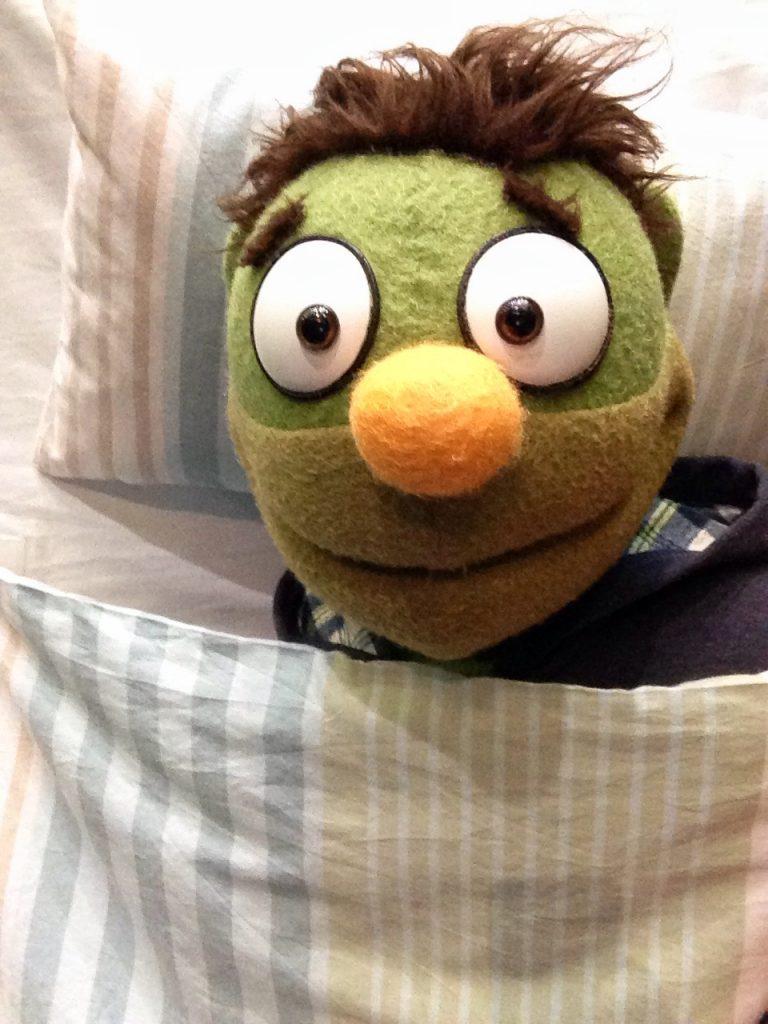 Puppe Nicky liegt gemütlich im Bett